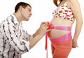 image photo : Man making a bow on a belly of pregnant woman