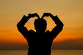 Man making heart shape.
