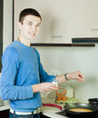 Man making scrambled eggs in frying pan at home kitchen Royalty Free Stock Images