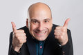Man making a silly face and giving thumb up bald isolated on gray Royalty Free Stock Photography