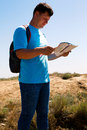 Man with map exploring wilderness on trekking adventure Royalty Free Stock Photo