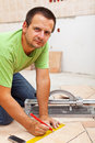 Man marking and cutting ceramic floor tiles kneeling near a cutter device Stock Photo