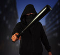 Man in the mask holds bat outdoor dangerous with baseball ready for fight night city Stock Photos