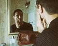 Man massaging cheek in front of mirror with brown leather toiletry bag vintage film camera photo grain a shaved military crew cut Royalty Free Stock Photos