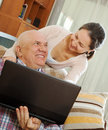 Man and mature woman working at his laptop happy couple shopping home via internet Royalty Free Stock Image
