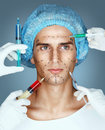 Man in medical hat and beauticians hands with syringes making botox injection in his face. Royalty Free Stock Photo