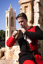 Man in a medieval suit plays a flute wooden on agia napa monastery background Stock Image