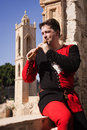Man in a medieval suit plays a flute wooden on agia napa monastery background Stock Photography