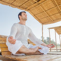 Man meditating doing yoga asana in a lotus position Royalty Free Stock Image