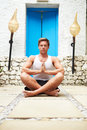 Man meditating outdoors at health spa facing camera Stock Image