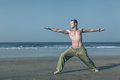 Man meditating in warrior pose young doing yoga and at sea beach Stock Images