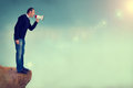 Man with megaphone shouting from cliff edge a loudhailer or of a Royalty Free Stock Photos