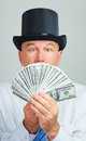Man with money surprised and amazed middle aged in a retro top hat focus on the cash Stock Images