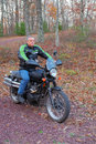 Man on a motorcycle is shown his in the woods enjoying his sport and the outdoors Stock Photos
