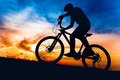 Man on mountain bike at sunset, riding bicycle on hills Royalty Free Stock Photo