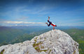 Man on mountain top handstanding summit Royalty Free Stock Photos