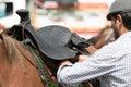 Man mounting saddle on horse back in Ecuador Royalty Free Stock Photo
