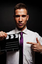 Man with movie clap over dark background looking at camera Royalty Free Stock Photo