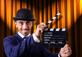 Man with movie clapper on curtain background Stock Images