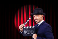 Man with movie clapper on curtain background Royalty Free Stock Photo
