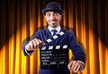 Man with movie clapper on curtain background Stock Photos