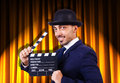 Man with movie clapper on curtain background Royalty Free Stock Images