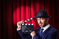 Man with movie clapper on curtain background Royalty Free Stock Image