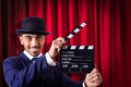 Man with movie clapper on curtain background Stock Photo