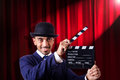 Man with movie clapper on curtain background Stock Image