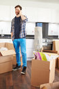 Man moving into new home talking on mobile phone in kitchen Royalty Free Stock Photography