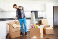 Man moving into new home talking on mobile phone looking in box Royalty Free Stock Photo