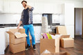Man moving into new home talking on mobile phone standing next to brown boxes Stock Photography