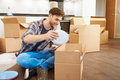 Man moving into new home and unpacking boxes sitting on floor holding white plate Royalty Free Stock Photography