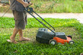 A man mow grass at his backyard by lawn mower machine Stock Photography