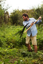 Man mowing grass with a scythe beard Royalty Free Stock Images