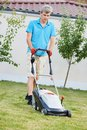Man mowing lawn adult cutting grass in his garden yard with mower Royalty Free Stock Images