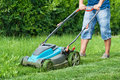 Man mowing the lawn with blue lawnmower in summertime Royalty Free Stock Photo