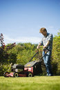 Man mowing lawn handsome young the on a beautiful sunny spring day shot in portrait format Royalty Free Stock Image