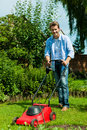 Man is mowing the lawn in summer young with a machine Royalty Free Stock Photos