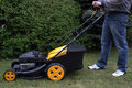 A man mows the grass with a gasoline mower