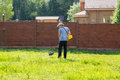 Man mows the grass with string trimmer Royalty Free Stock Photo