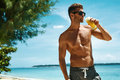 Man with muscular body drinking healthy drink on beach summer handsome fitness male model having fun enjoying travel vacation Royalty Free Stock Images