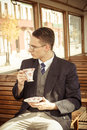 Man with mustache and glasses on train wooden wagon drinking cof Royalty Free Stock Photo