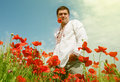 Man in national ukrainian embroidered dress among the poppies fl Royalty Free Stock Photo