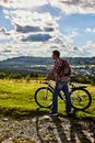 stock image of  A man in nature with a bicycle on the background of mountains and blue sky