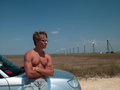 Man near the car handsome young with a naked torso Royalty Free Stock Photo