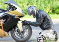 Man near a motorcycle on his knees sports bike on the road Royalty Free Stock Photo