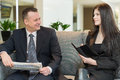 A man with newspaper and women with notepad talking men about business Royalty Free Stock Image