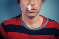 Man with nose bleed and cold sores young tissue in his nostril has as well as on his lip Stock Photo