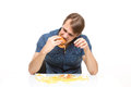 Man is not careful eating tasteless burger drops potatoes Royalty Free Stock Images
